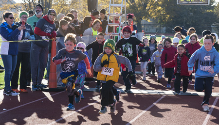 West Islip, NY, USA - 24 November 2017: The start of the kids fun run on a red track with their parents cheering them on at a local turkey trot race on Thanksgiving weekend. Redakční