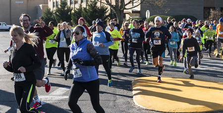 West Islip, NY, USA - 24 November 2017: The middle of the pack of a group of runners racing a local turkey trot on Thanksgiving weekend.