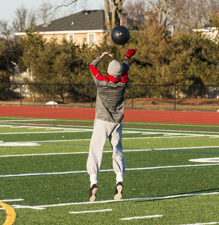 A high school track and field athlete is training for strength and speed by throwing a 10 pound medicine ball over his head while jumping outside on a turf field.