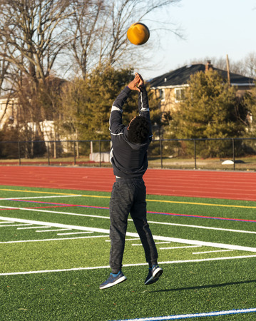 A high school track and field athlete is jumping in the air while throwing a medicine ball over his head backwards on a green turf field.