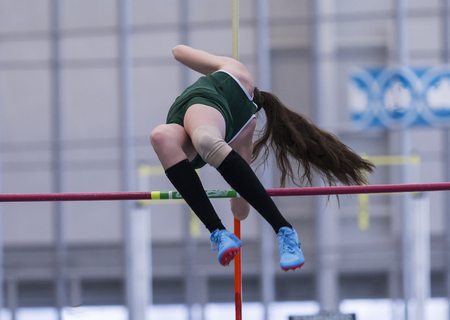 A high school girl is clearing the bar during a pole vault competition at a track meet.