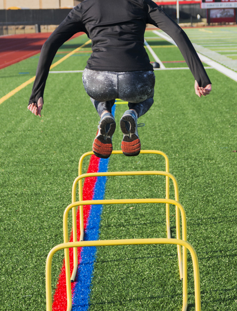 A high school track and field sprinter is jumping over yellow banana hurdles for strength and stability during practice on a green turf field on a cool afternoon.