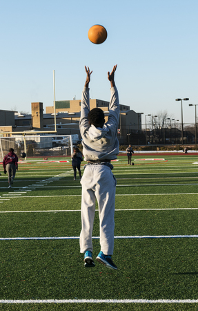 A male high school track and field athlete throwing a medicine ball in the air and jumping off of the ground during speed training drills.