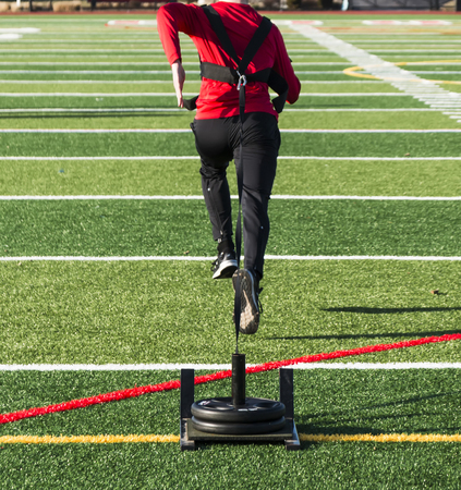 A track and field runner is pulling a weighted sled across a green turf field for speed and strength training.