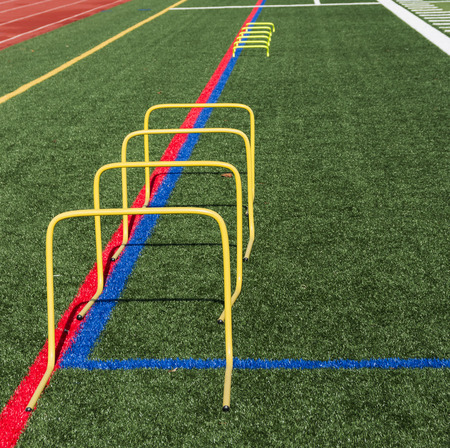 Four 24 inch yellow banana step hurdles are set up on a turf fied for athletes to jump over followed by some 6 inch yellow hurldes to run over at speed training practice.