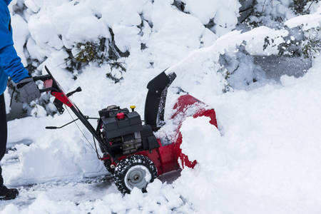 A young man is clearing his neighbors driveway with his small snow blower after a spring snow storm.