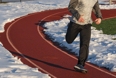 A runner is running on a track surrounded by snow and is over pronating so badly that it looks like he is rolling his ankle. 版權商用圖片