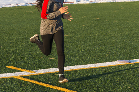 A high school female runner is running fast on a green turf field iin the winter, with snow lining the track behind her. Imagens