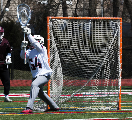 A lacrosse goalie is blocking the net and stopping the ball from going into the goal during a high school lacrosse game.