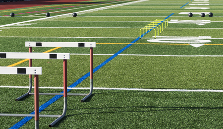 Athletic turf field set up for speed, strength and agility practice with hurdles, medicine balls and mini yellow banana hurdles. Stockfoto