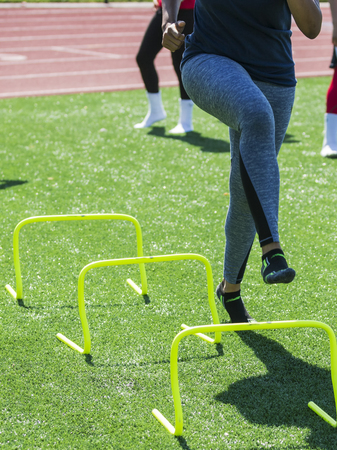 A runner is performing speed drills ovr yellow mini banana hurdles with no shoes on during trak and field practice.