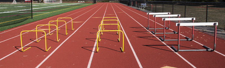 A red track is set up for athletes to jump over yellow mini hurdles and regular hurdles. Standard-Bild