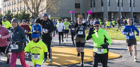 West Islip, NY, USA - 24 November 2017: Runners wave to the camera at the start of the Run Your Turkey Off 4K race, the day after thanksgiving.