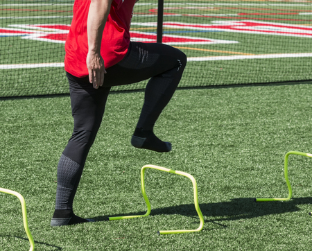 A high school track sprinter is in a-position while stepping over yellow mini banana hurdles on a green turf field during practice. Standard-Bild