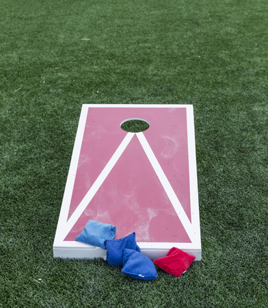 A red and white wooden cornhole game is on green turf with blue and red bean bags.