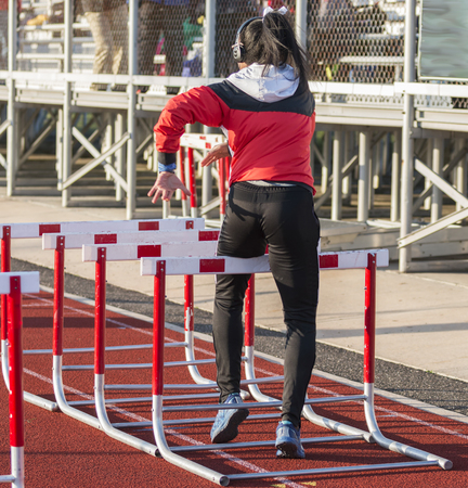 A high school girl os warming up for a hurdle race by performing hurdle walk over drills while wearing head phones.
