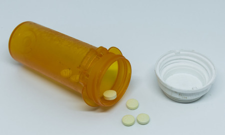 A prescription pill bottle of oxycodone is laying on its side with pills coming out on to the ground with a white background.