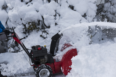 A snow blower is clearing a driveway after a winter blizzard on long island.