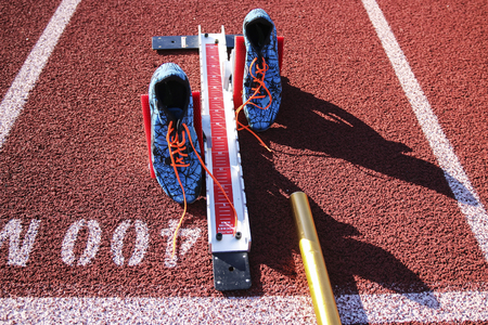 Starting blocks are set on at the 400 meter starting line wigh spikes and a baton on a red track.