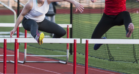 Two high school girls racing each other in the hurdles during a track and field race. Stock fotó
