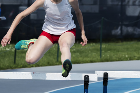 A high school girl is racing the 400 meter hurdles on the turn before the final straightaway. Stok Fotoğraf - 104947548