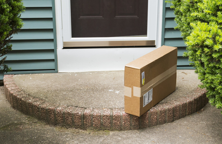 A brown cardboard box is left on the front stoop after being delivered while no one was home. Imagens - 106351672