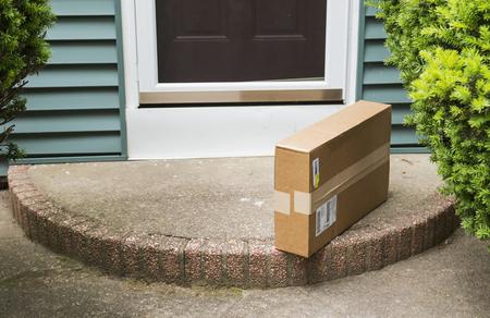 Een bruine kartonnen doos wordt op de voorstoep achtergelaten nadat hij is afgeleverd terwijl er niemand thuis was.