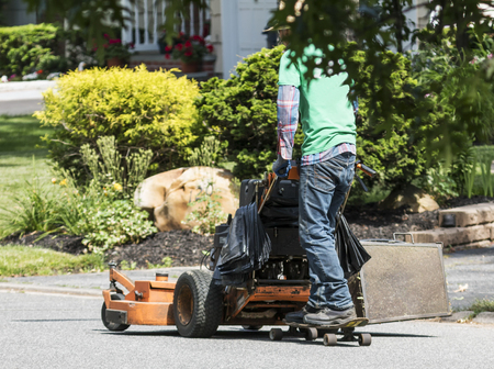 A landscaper is getting to another job by riding behind his lawnmower with a skateboard on the road. Banque d'images - 106352013