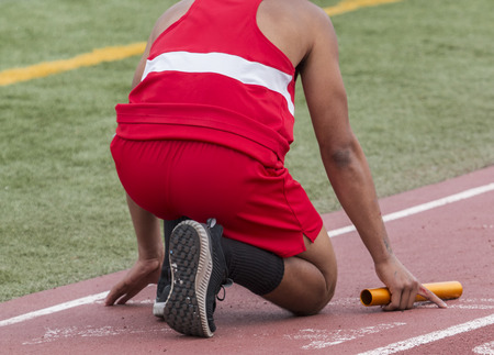 A high school runner is in the on your mark position ready to start a relay race at a track and field competition. 写真素材
