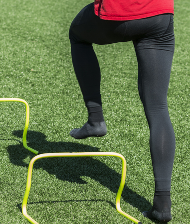 A high school track athlete is not wearing shoes while performing speed and agility drills in black socks on a gren turf field.