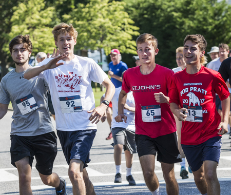 Bay Shore, NY, USA - 16 June 2018: Four runners wave to camera while racing the Run For PWS fundraiser on the roads. Sajtókép