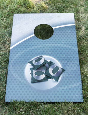 An metal aqua colored corn hole board is on green grass with green bean bags on it.