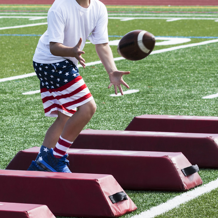 A young boy is at summer football camp catching a football while running sideways over red barriers and wearing red, white and blue flag shorts and socks.