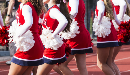 High school cheerleaders are cheering during a football game.