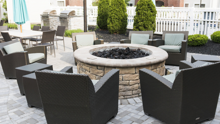 A hotels patio is set up with a fire pit and chairs with tables and umbrelllas and a barbeque grill for friends and families to relax,