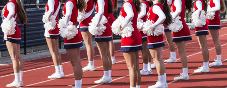 Cheerleading squad performing a routine in fron of the home fans at a high school football game. Stock Photo