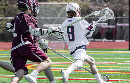 A high school boy lacrosse player is running down the field with the ball in his stick, being chased by the competition.