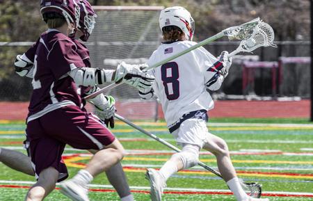 Ein Lacrosse-Spieler eines Highschool-Jungen rennt mit dem Ball im Schläger über das Feld und wird von der Konkurrenz verfolgt.