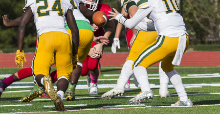 The quarterback is receiving the ball in the shot gun during a high school football game. Stock Photo