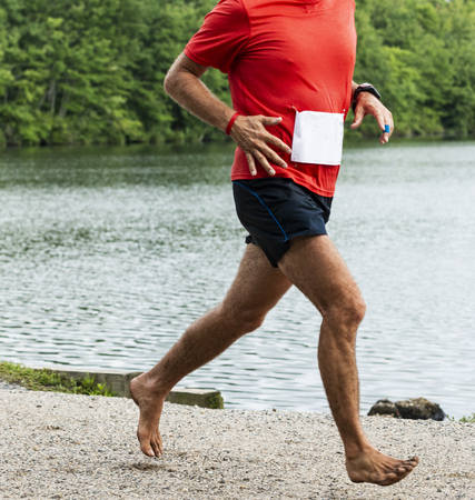 Babylon, New York, USA - 12 August 2018: A runner is running a 10,000 meter race with no shoes on, off road in the trials passing a lake during the Dirty Sock Fundraiser run.