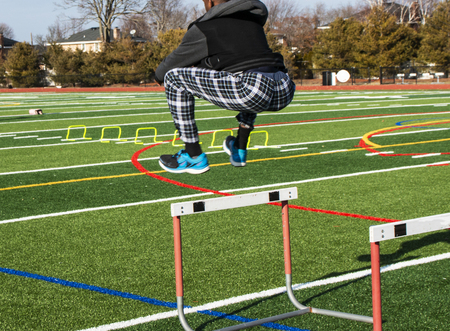 A high school boy is jumping over hurdles on a turf field during strength, agility and speed practice on a cold day. Standard-Bild - 109618301