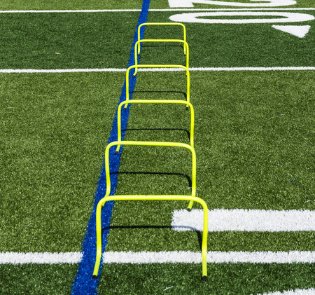 Six yellow mini hurdles are set up on a green turf field as part of a teams speed and agility practice. Standard-Bild - 109618351