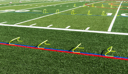 Six and twelve inch yellow mini hurdles are set up on a green turf field for speed and agility practice. Reklamní fotografie