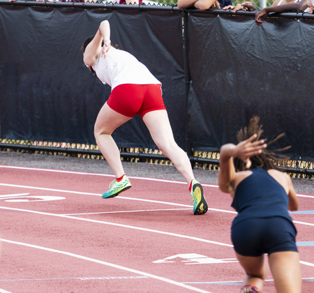 Two high school femal sprinters are starting a race in lanes four and five on a red track during a track and field sprint race.