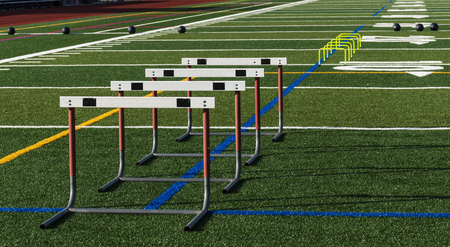 A green turf football field has hurdles and medicine balls set up for strenght, speed and agility practice. Standard-Bild - 109618805
