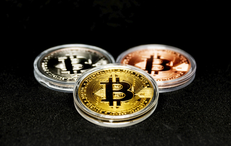Three bitcoins, gold, silver and bronze with a black background in clear protective cases.