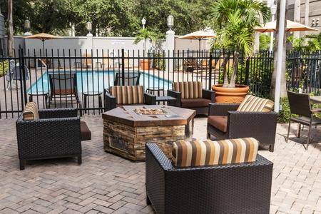 De patio van een hotel is ingericht met een vuurplaats, een zwembad en meubels om te ontspannen tijdens uw verblijf.