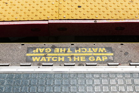 Watch the gap is painted in yellow to warn customers on the Long Island Railroad platform. 免版税图像