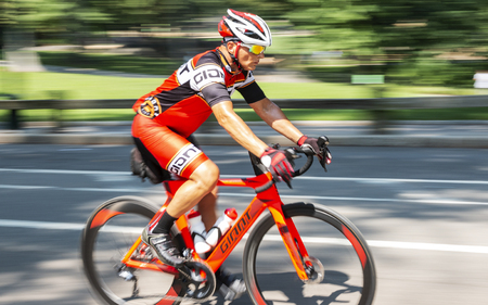 New York City, USA - 15 August 2018: A man is training on a road racing bike in central park with the background blurred and wheels look like they are moving.