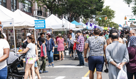 Astoria, New York, USA - 29 July 2018: Many vendors line both sides of the steet selling their artwork and crafts at a street fair in Astoria Queens New York City.